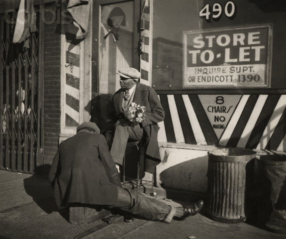 ca. 1924, Manhattan, New York City, New York State, USA --- A man holding a bouquet of flowers gets a shoeshine on the sidewalk in front of a barbershop up for rent. --- Image by © E.O. Hoppé/Corbis